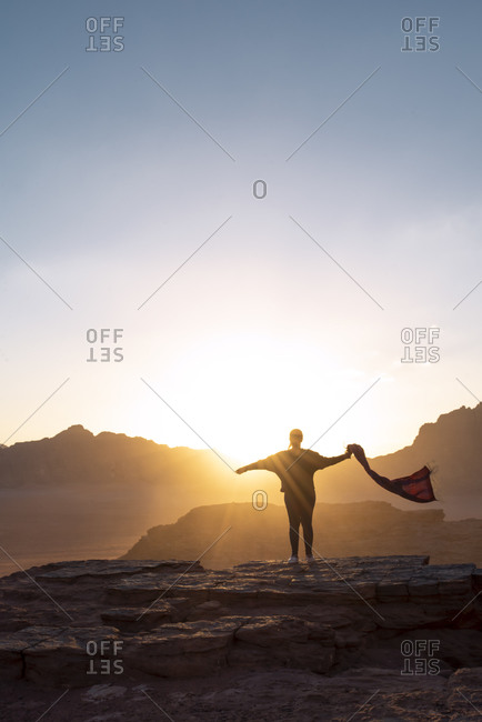 Silhouette of tourist standing with outstretched arms on rocky hill and admiring magnificent sundown white enjoying freedom in Jordan