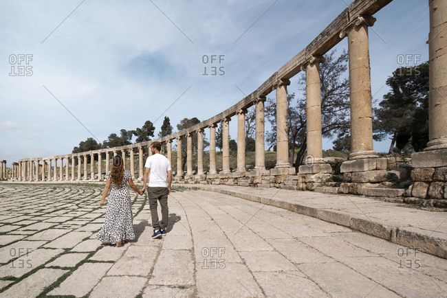 Back view of loving couple of tourists holding hands and walking along Oval Plaza in Jerash during summer vacation in Jordan