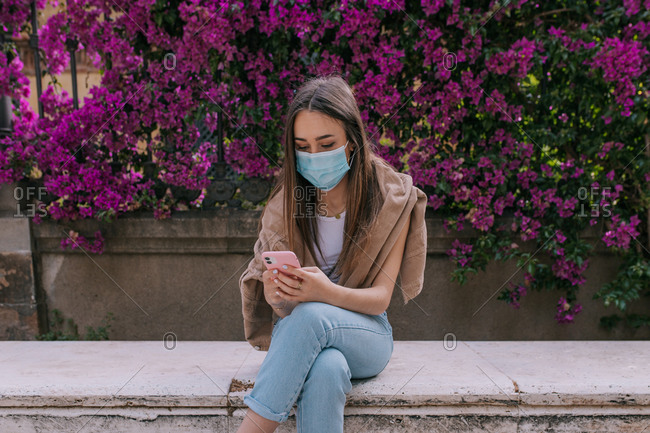 Young woman using the smartphone at the park wearing a face mask outdoors during a pandemic