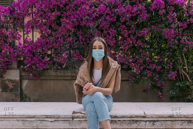 Young woman at the park wearing a face mask outdoors during a pandemic