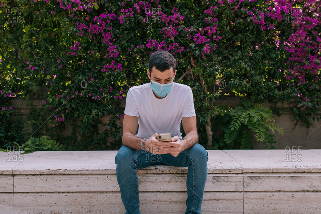 Young man using the smartphone at the park wearing a face mask outdoors during a pandemic