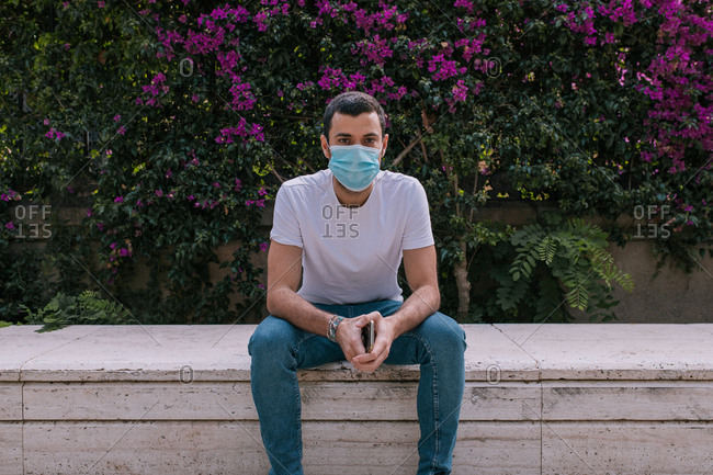 Young man at the park wearing a face mask outdoors during a pandemic