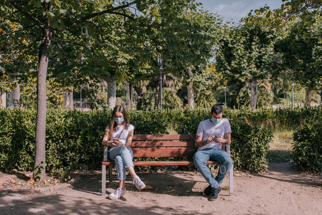 Couple at the park using the smartphone, wearing face masks and respecting social distancing during a pandemic
