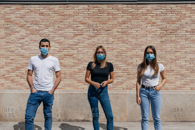 Three friends outdoors wearing face masks and respecting social distancing during a pandemic