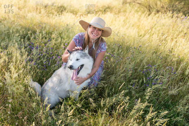 Delighted female in summer dress and straw hat relaxing on meadow with Alaskan Malamute and looking at camera