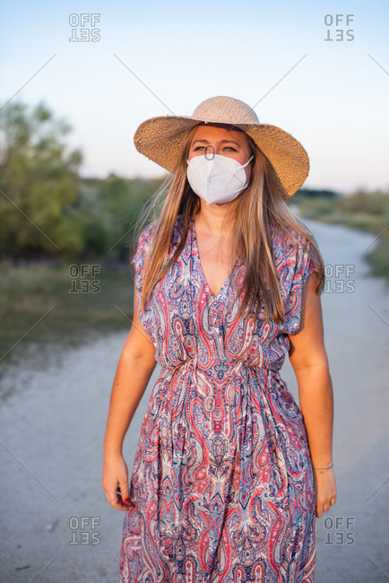 Carefree female wearing protective mask standing on rural road and enjoying sundown during coronavirus epidemic