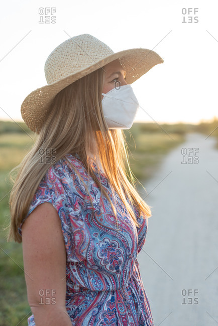 Side view of carefree female wearing protective mask standing on rural road and enjoying sundown during coronavirus epidemic