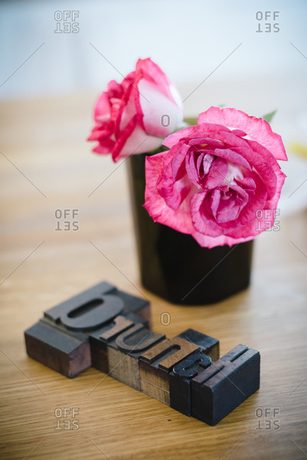 Blooming pink roses in black pot arranged near Brunch inscription on wooden table