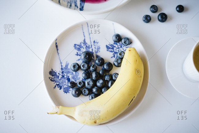 Top view of fresh blueberries and a banana served with cup of coffee on table setting for home brunch in cozy kitchen