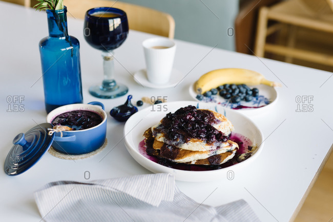 From above delicious homemade pancakes with blueberry jam served with cup of coffee and fresh berries and banana on table setting for home brunch in cozy kitchen