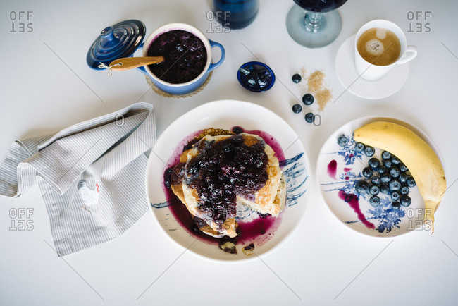 Top view of delicious homemade pancakes with blueberry jam served with cup of coffee and fresh berries and banana on table setting for home brunch in cozy kitchen