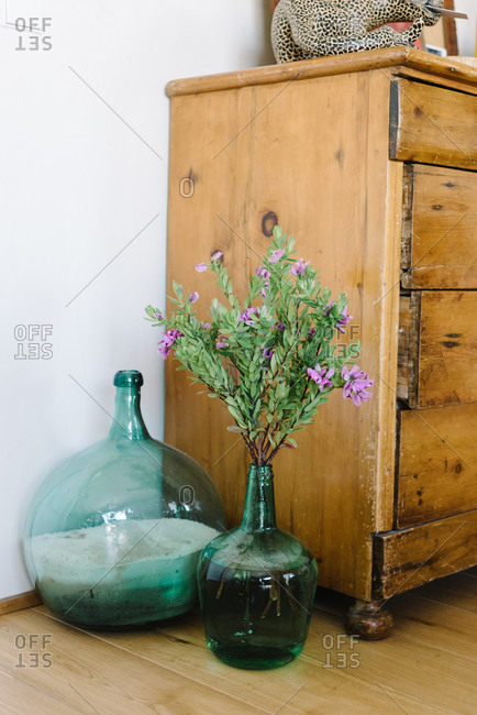 Set of various glass vases with flowers and sand arranged near weathered wooden cabinet in cozy room with retro interior design