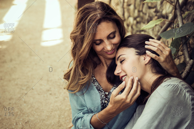 Crop of front view of charming young daughter and slender middle aged mother hugging tenderly in green garden in summer