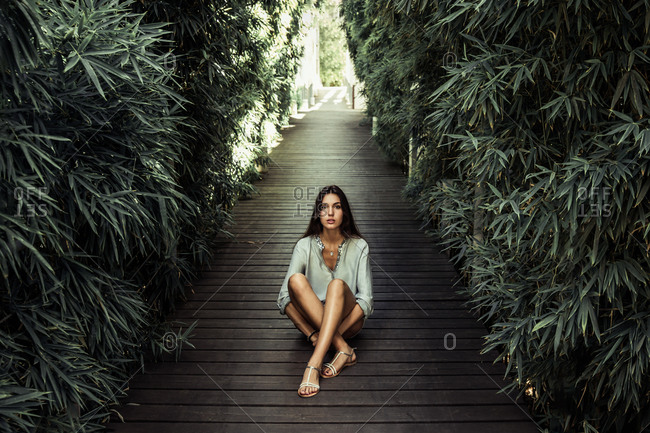 Peaceful female in casual wear relaxing on wooden pathway surrounded by green trees on sunny day in summer and looking at camera