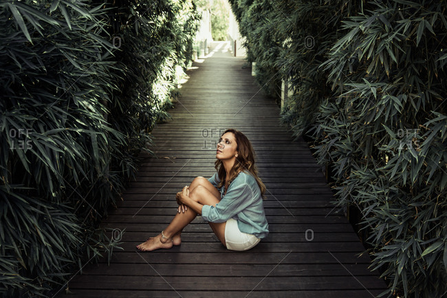 Peaceful middle-aged female in casual wear relaxing on wooden pathway surrounded by green trees on sunny day in summer and looking away