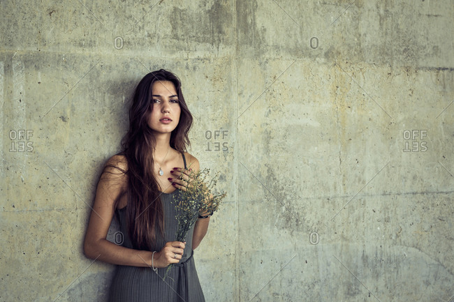 Serene female with long hair standing near stone wall with bouquet of fresh flowers and looking at camera