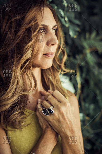 Pensive female with wavy hair and in summer clothes standing with hands on chest in garden and looking away