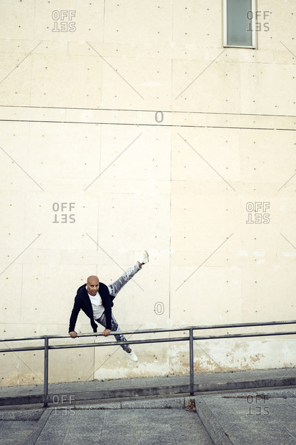 Flexible male in casual wear performing trick on metal railing while jumping and doing parkour