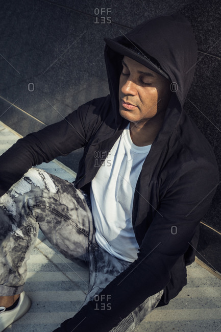 High angle of ethnic man in fashionable clothes sitting on pavement and leaning on wall of building