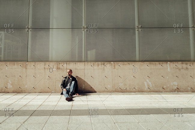 Modern young bearded hipster guy in casual black jacket and ripped jeans looking away while sitting against a concrete wall