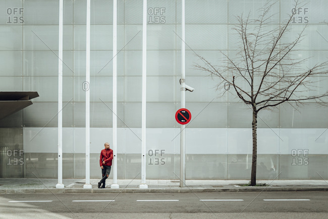 Full body stylish young guy in red warm jacket and jeans standing near metal poles with prohibition sign against modern building with glass wall