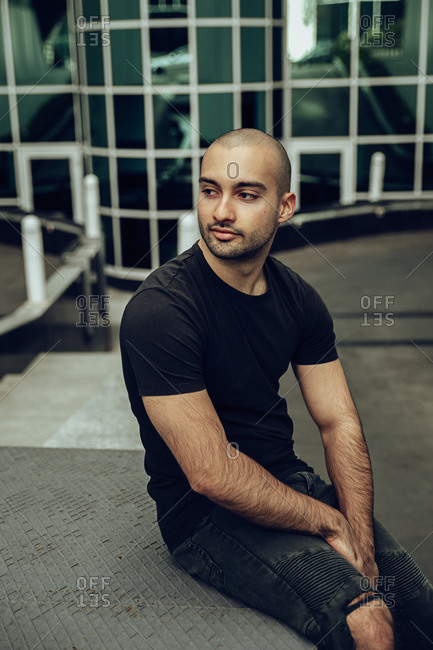 Modern young bearded hipster guy in casual black shirt and ripped jeans looking away while sitting on stairs near contemporary building