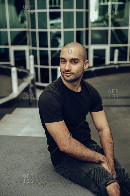 Modern young bearded hipster guy in casual black shirt and ripped jeans smiling and looking at camera while sitting on stairs near contemporary building