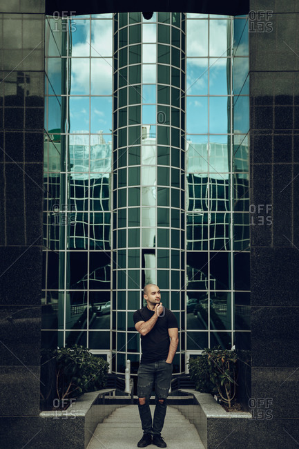 Full body of pensive young male in trendy outfit touching chin while standing against contemporary city building with glass wall and looking away