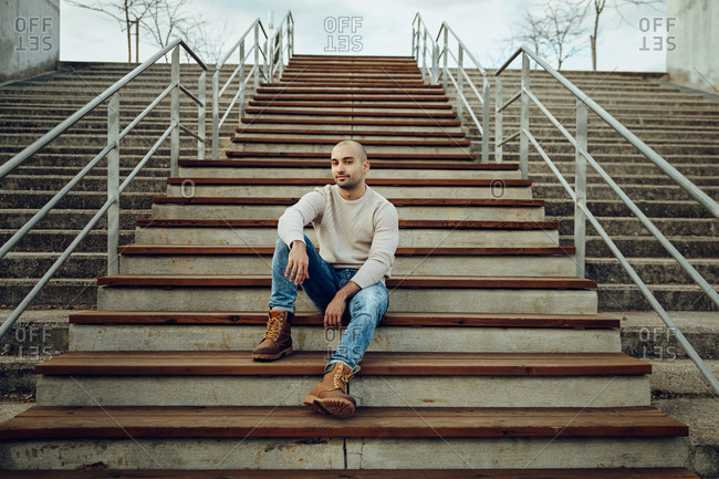 From below full length of positive young unshaven male in casual sweater and jeans with trendy boots sitting on stairway on street and looking at camera