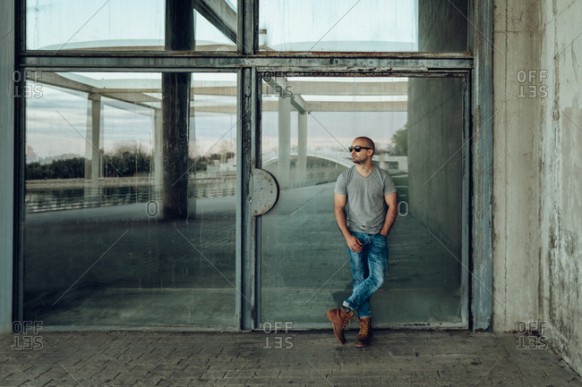 Full body confident young male in trendy outfit and sunglasses looking away while standing against glass wall of aged building