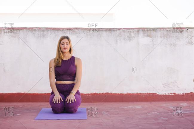 Female meditating in Vajrasana with eyes closed
