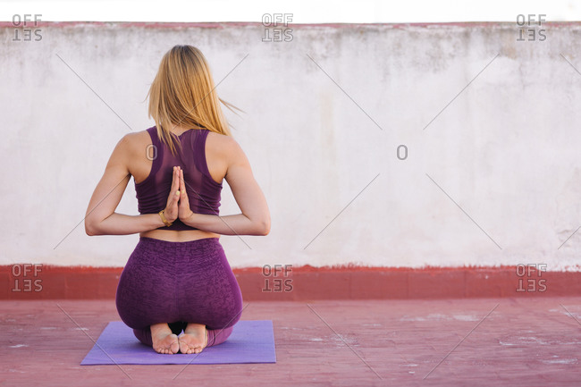 Back view of unrecognizable female meditating in Vajrasana with Namaste gesture behind back