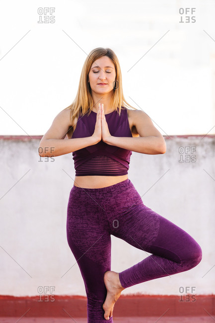 Concentrated female in sportswear balancing on leg in Vrksasana and doing yoga while standing with closed eyes and Namaste gesture