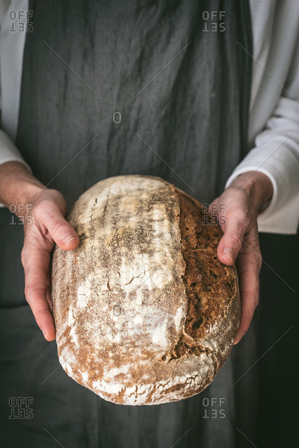Cropped unrecognizable baker in apron with loaf of tasty bread placed