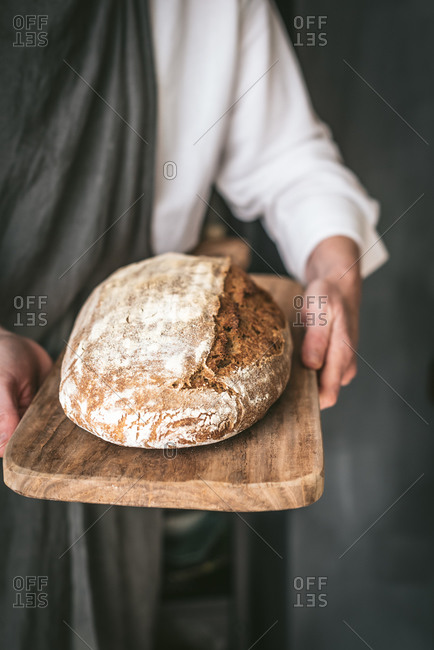 Unrecognizable baker in apron with loaf of tasty bread placed on wooden cutting board