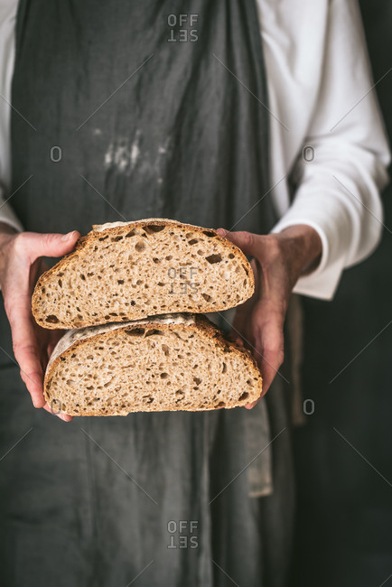 Cropped unrecognizable baker in apron with loaf of tasty bread cut in half placed