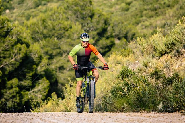 Man in helmet riding mountain bike in forest