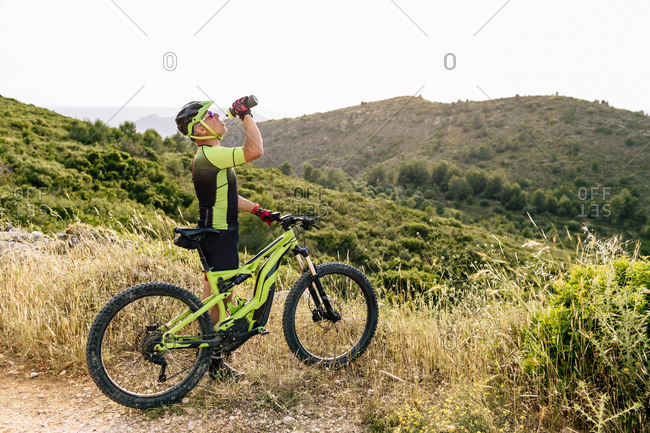 Man in helmet drinking water near bike in mountain