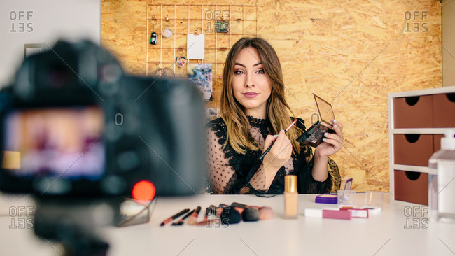 Charming female influencer in elegant wear standing with palette of eyeshadow and cosmetic brush while looking at camera making a tutorial recording video on professional camera