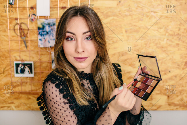 Charming female influencer in elegant wear standing with palette of eyeshadow and cosmetic brush while looking at camera making a tutorial