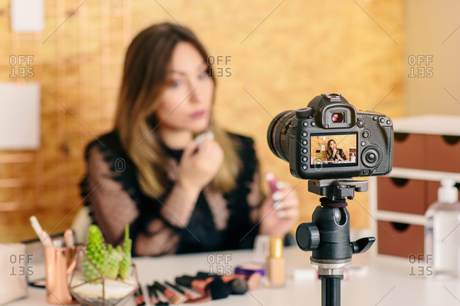 Charming female influencer in elegant wear applying lipstick while looking at camera making a tutorial recording video on professional camera