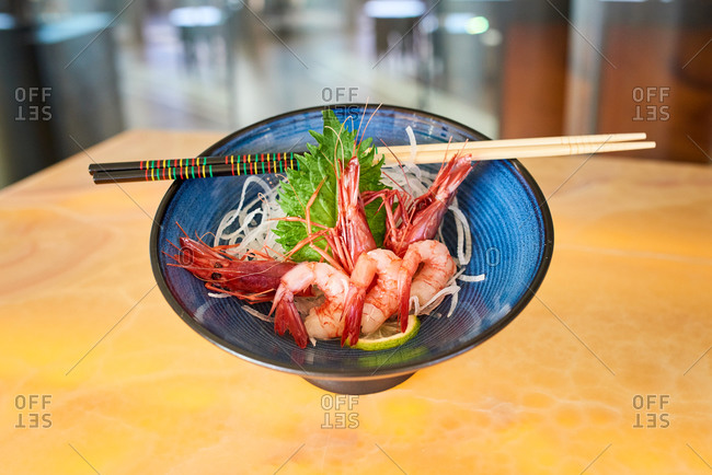 Traditional Sashimi with prawns served with daikon and slice of fresh lime and placed on table