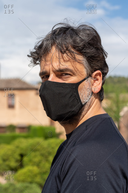 Portrait of a man wearing medical mask and looking at camera outdoors