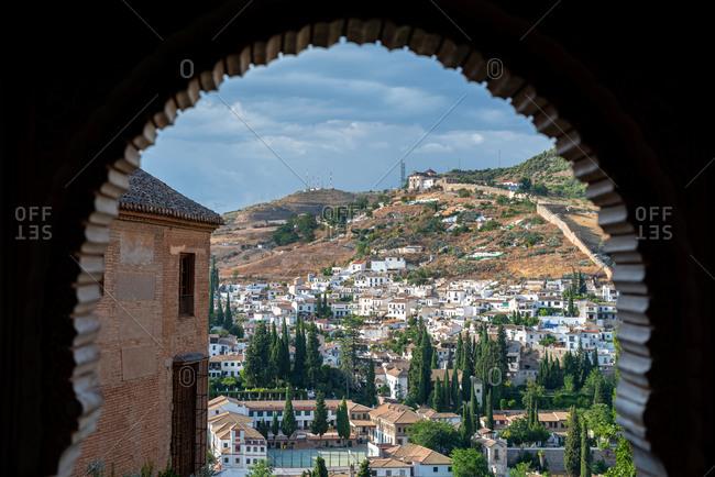 Alhambra arch and Granada cityscape on the background. Granada, Spain