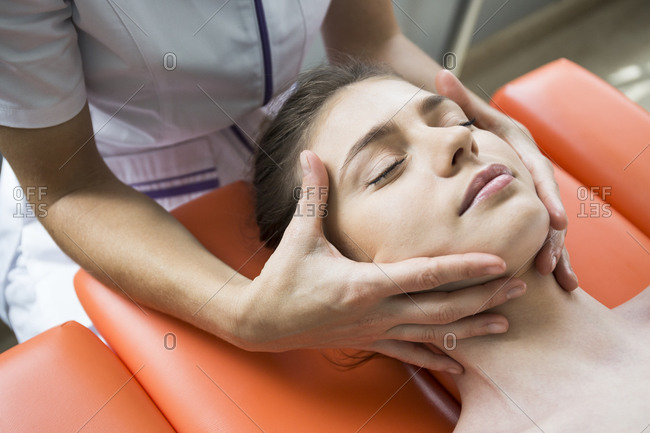 Hands of female physiotherapist massaging the face of a woman