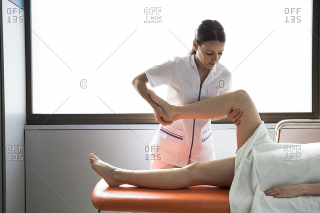 Female physiotherapist treating leg of female patient