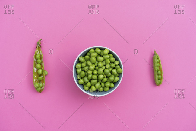 Studio shot of two green pea pods and bowl of green peas