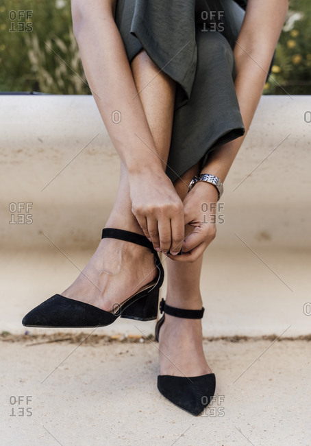 Close-up of woman legs wearing sandals sitting on seat in city