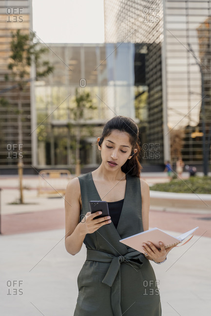 Businesswoman holding note pad using smart phone while standing in city