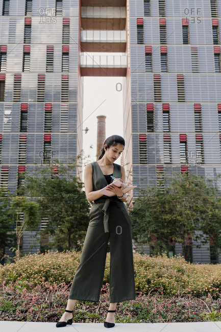 Female professional writing in note pad while standing against modern building